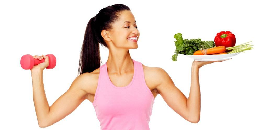 Woman holding weights and vegetables